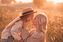 Young Mother And Her Daughter Look At Each Other With Love In The Countryside