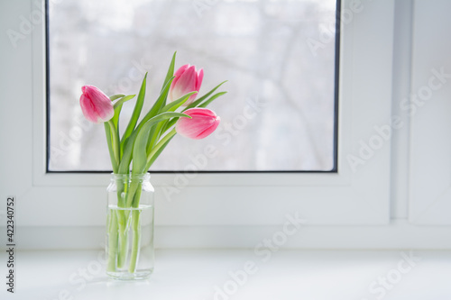 Obraz na płótnie A bouquet of pink tulips in a glass jar is on the windowsill in the house
