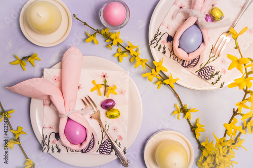 Obraz na plátne Easter table decorated with napkins and egg as an Easter bunny, egg candles and