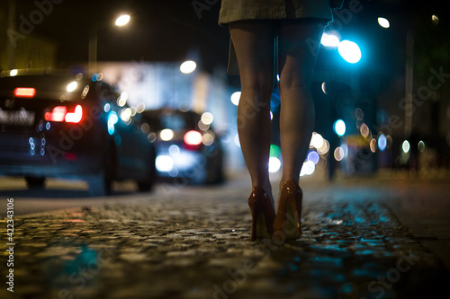 Fotografia, Obraz Shapely female legs in high heels on the street against the background of the lights of moving cars