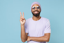 Young Smiling Happy Positive Student Fun Unshaven Black Dark-skinned African Man In Violet T-shirt Purple Hat Glasses Show Victory V-sign Gesture Isolated On Pastel Blue Background Studio Portrait