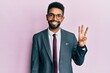 Handsome hispanic business man with beard wearing business suit and tie showing and pointing up with fingers number three while smiling confident and happy.
