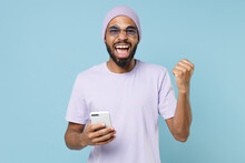 Young Unshaven Student Black African Man 20s In Violet T-shirt Purple Hat Glasses Using Mobile Cell Phone Do Winner Gesture Clench Fist Celebrating Isolated On Pastel Blue Background Studio Portrait