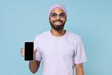 Young Smiling Happy Satisfied Black African Man In Violet T-shirt Purprle Hat Glasses Show Mobile Cell Phone, Blank Screen Workspace Area Mock Up Isolated On Pastel Blue Background Studio Portrait