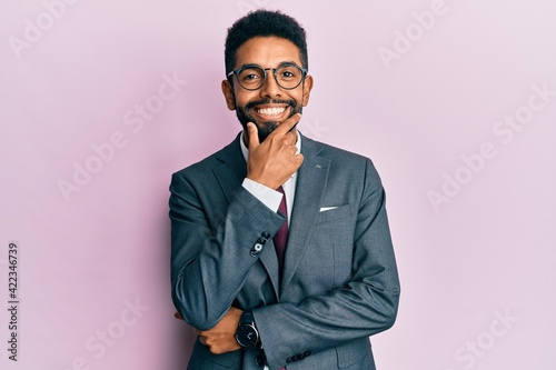 Obraz Handsome hispanic business man with beard wearing business suit and tie looking confident at the camera smiling with crossed arms and hand raised on chin. thinking positive. - fototapety do salonu