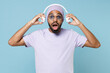 Young surprised shocked impressed unshaven black african man 20s wear violet t-shirt hat glasses listening to music with took off headphones isolated on pastel blue color background studio portrait