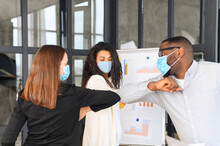 Diverse Work Team In Protective Medical Masks Greet Each Other With Elbows Instead Of Shaking Hands Standing In Contemporary Office Space. Safety Measures For Office Employment