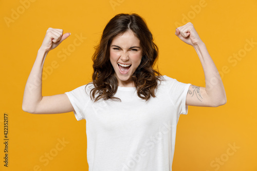 Young caucasian happy strong sporty woman 20s wear white basic blank print design casual t-shirt show biceps muscles on hand demonstrating strength power isolated on yellow background studio portrait Fototapet