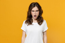 Young Shocked Impressed Angry Indignant Scared Student Woman 20s In White Basic Blank Print Design Casual T-shirt Look Camera With Opened Mouth Isolated On Yellow Orange Background Studio Portrait.