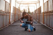 A Brutal Bearded Male Guitarist In A Brown Leather Jacket And Blue Jeans Sits With His Knees On The Asphalt And Holds A Black Electric Guitar Against The Background Of A Road And An Iron Fence