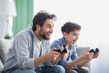 Stay At Home With Fun. Happy Dad And Son Competing With Each Other In Video Games