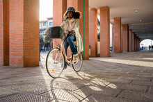 Young Commuter Woman In City In Sustainable Way Wearing Bike Helmet With Protective Face Mask Against Coronavirus Covid-19 Pandemic Rides Her Bicycle On Way Home To Work - Safety And Commuting Concept