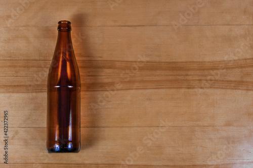 Obraz Brown glass empty beverage bottle lying vertically on wooden background - fototapety do salonu