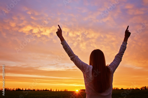 woman feeling victorious facing the beautiful sunset.