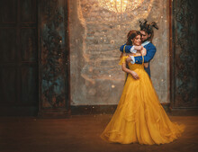 Couple Embrace In Room Old Castle. Happy Beauty Woman Fantasy Princess In Yellow Dress And Guy Is Enchanted Beast, Horns On Head. Romantic Male Prince Hugs Girl In Arms. Man Monster Carnival Costume.