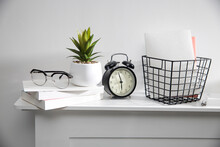 A Stack Of Books, An Artificial Succulent Plant In A Ceramic Pot, Glasses, A Metal Basket With Notebooks, A Pen Are On A White Table Surface. Concept - Office At Home. Online Training.