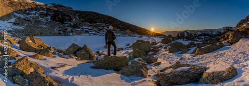 panoramic view of the sunrise or sunset of the sun over the mountains with a snow lake with a unrecognized person #422390708