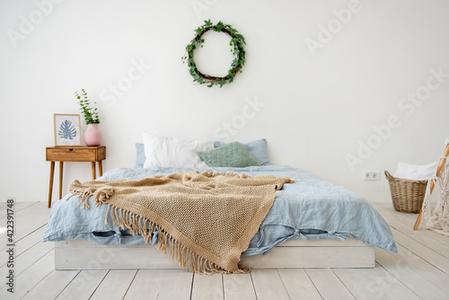 Fototapeta Stylish, trendy interior in Scandinavian style. In a white loft room, a bed on the floor with a blue bed, brown rug, a wicker wreath on the wall with ivy, wooden bedside table with a vase. Copy space obraz na płótnie