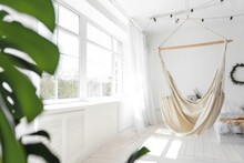 Stylish, Trendy Interior In Scandinavian Style. Large Wooden Window Sees White Macrame Hammock Against The Backdrop Of Green Monstera, Bed On The Floor. Garland Of Light Bulbs Hangs From The Ceiling.