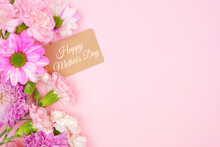 Happy Mothers Day Gift Tag With Side Border Of Pink And White Flowers. Top View On A Pink Background. Copy Space.