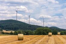 Feld Mit Drei Strohballen Vor Bewaldetem Berg Mit Drei Windkraftanlagen