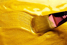 Beautiful Abstract Golden Liquid Paint Background With Brush, Beauty Gold Backdrop Texture. Metallic Gold Paint, Art Design. Yellow Shimmering Surface Close-up. Golden Bright Glitter Texture