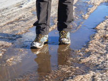 Trekking Boots In The Muddy Spring. The Ice Melts In The Spring, A Man Walks Through Puddles On The Street, Spring Weather