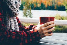 Woman Enjoying Coffee - Hot Drink - While Sitting Lakeside Outdoors In Autumn. Closeup, Blurred Background, Filtered Effect