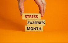 Stress Awareness Month Symbol. Wooden Blocks With Words 'Stress Awareness Month'. Beautiful Orange Background. Doctor Hand. Psychological, Business And Stress Awareness Month Concept. Copy Space.