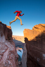 A Man Jumping Across A Chasm At Horseshoe Bend Overlook At Sunrise, Page, Arizona.