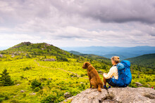 A Woman And Her Dog Hiking The Wilburn Ridge Tail Section Of The Appalachian Trail, Grayson Highlands, Mouth Of Wilson, Virginia.