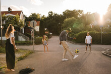 Father Playing With Soccer Ball With Family On Road