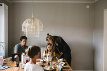 Mother Kissing Daughter Over Dining Table At Home