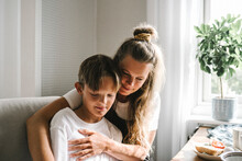 Smiling Mother Embracing Son At Home