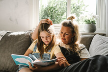 Daughter Writing In Book While Sitting By Mother On Sofa At Home