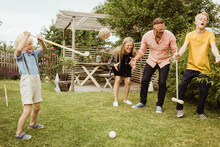 Cheerful Family Playing Polo In Front Yard