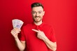 Young redhead man holding 20 polish zloty banknotes smiling happy pointing with hand and finger