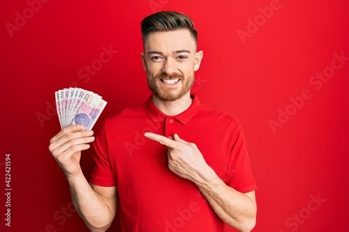 Fototapeta Young redhead man holding 20 polish zloty banknotes smiling happy pointing with hand and finger obraz