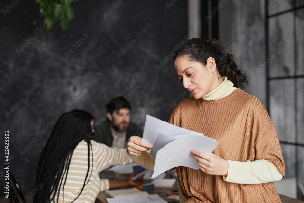 Fototapeta Waist up portrait of elegant Middle-Eastern businesswoman reading documents in office with diverse group of people meeting in background, copy space