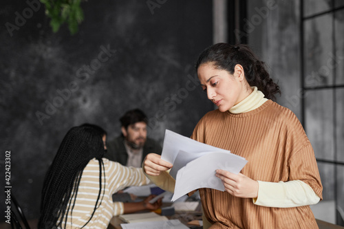 Obraz Waist up portrait of elegant Middle-Eastern businesswoman reading documents in office with diverse group of people meeting in background, copy space - fototapety do salonu