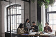Wide angle view at multi-ethnic group of business people discussing project while sitting at meeting table in graphic office interior, copy space