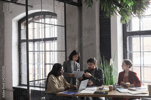 Fototapeta Wide angle view at multi-ethnic group of business people discussing project while sitting at meeting table in graphic office interior, copy space obraz