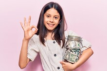 Beautiful Child Girl Holding Jar With Savings Doing Ok Sign With Fingers, Smiling Friendly Gesturing Excellent Symbol