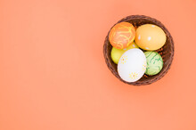 Top View Of A Basket With Various Easter Eggs Isolated On Orange Background With Space For Text