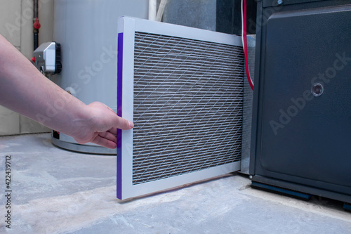 Canvas Print A person changing a dirty used air filter on a high efficiency furnace