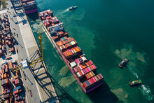 Aerial Top View Of Cargo Ship Transportation And Tug Boat Cargo Ship Leaving Harbor In Deep Sea Port At Industrial Estate For Import Export Around In The World, Business Logistic Transportation Sea