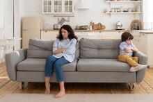 Annoyed Mom And Stubborn Child Sitting On Couch At Home, Ignoring Each Other, Posture Of Discontent. Sad Mother Disobedient Kid Son Sitting Apart On Sofa With Arms Crossed, Not Talking After Quarrel.