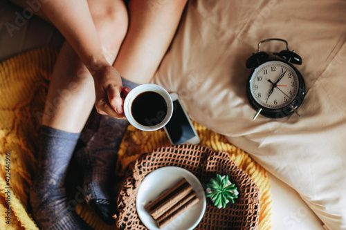 Fototapeta Top view of hand holding a cup of coffee with tasty snack for breakfast and clock showing 7 o'clock and feet in warm sock on the bed obraz