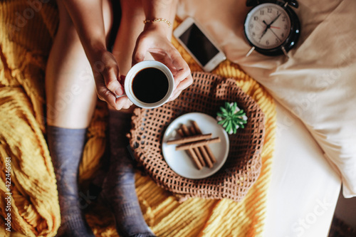Obraz Top view of hand holding a cup of coffee with tasty snack for breakfast and clock showing 7 o'clock and feet in warm sock on the bed - fototapety do salonu
