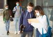 Leinwandbild Motiv Focused teenage girl and boy in face masks talking about homework after lessons near school outdoors